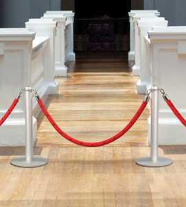 Interdiction d'accès au sein d'un musée à l'aide de poteaux de guidages à cordon.